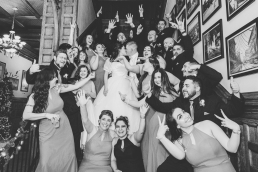 huge wedding party standing on stairs celebrating