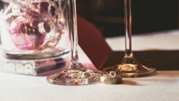 wedding rings in front of champagne glasses