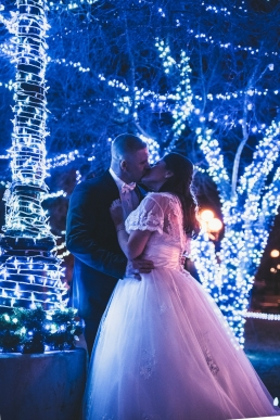 bride and groom kissing in front of blue lights