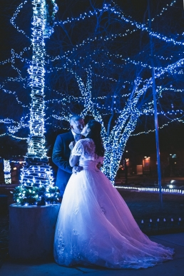 bride and groom in front of clue christmas lights
