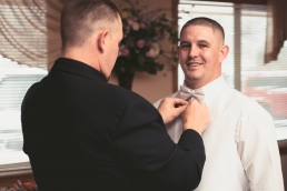 best man putting on grooms bow tie