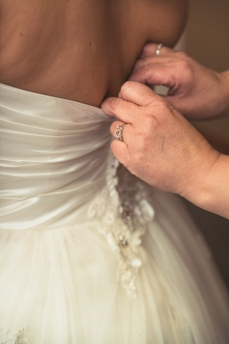 hands buttoning the brides dress