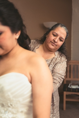 mother buttoning the brides dress