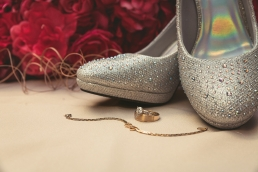 wedding rings and shoes and flowers detail shot