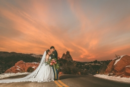 bride and groom standing on a road in garden of the gods colorado during sunset