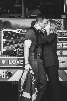 engagement photo of a couple kissing in front of a fire truck