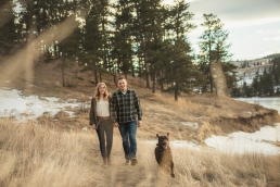 engagement couple walking in the tall grass in winter with a dog