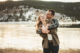 engagement couple hugging in the tall grass in winter